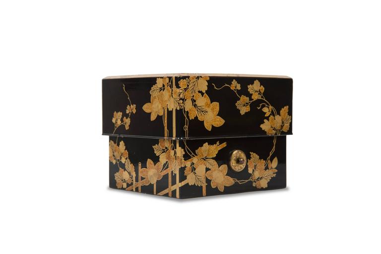 """Black background lacquer box with a decor of foliage and flowers. It contains a small tray supporting six assorted boxes with the symbols of the """"Tale of Genji."""" These small Kobako were intended to contain mixtures of scented woods or incense"""