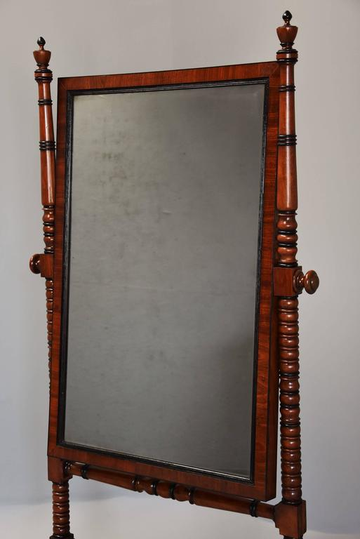 An early 19th century fine qualityRegency mahogany cheval mirror.  Themirror frame consists of an ebonized and reeded moulding with mahogany cross bandingsurrounded by ebony stringing, the mahogany panelled back confirming the superb quality of