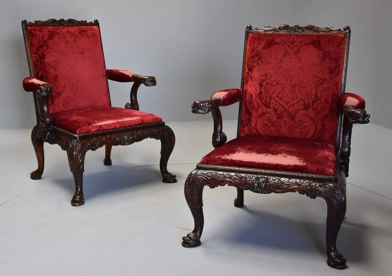 An exceptional pair of late 19th-early 20th century George II style mahogany Gainsborough open armchairs ( or library chairs) of large proportions with possibly the original upholstery.  This superb pair of chairs are copies of an original model