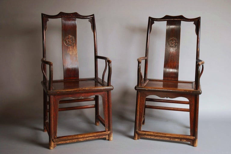 A pair of late 19th century Chinese yoke back elm armchairs of good patina. 
