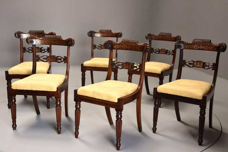 A fine quality early 19th century set of six Regency rosewood dining chairs with brass inlaid decoration.  Each chair consists of a shaped back rail with gadroon carved decoration with carved rosettes to each end with Fine quality inlaid brass