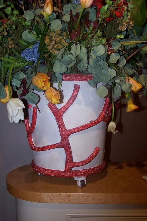 Painted iron and cast iron flower pot on castors. Fallen branches serving as handles.