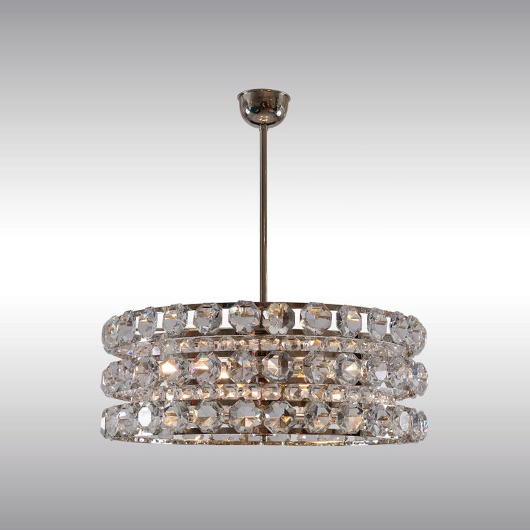 Very solid and heavy crystal chandelier from the 1960s. In three rows each with 26 very large, handcut glass prisms are arranged. 4 x 100W.