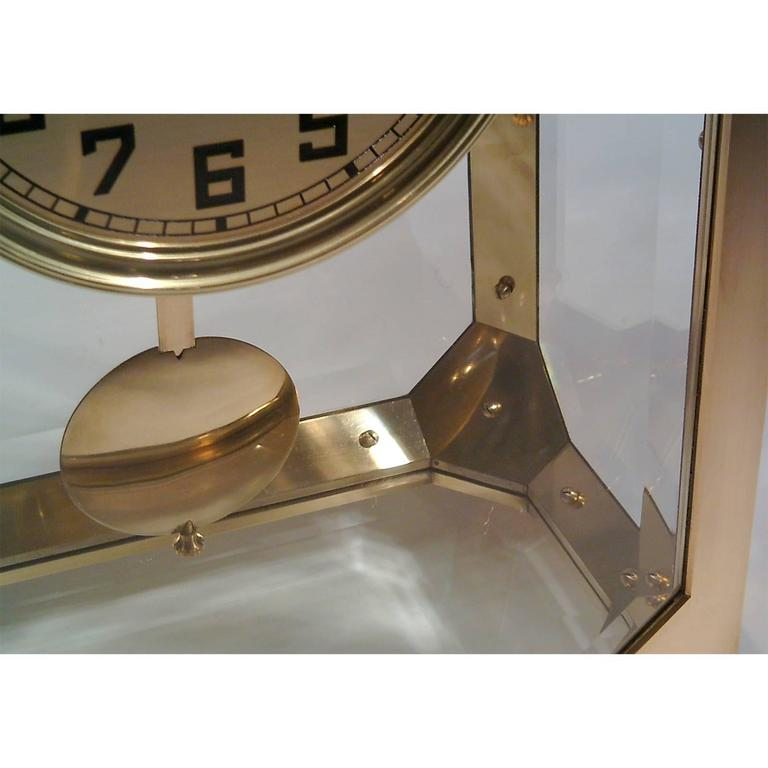 """Mantelpiece clock, often used by Adolf Loos in houses he designed. Casted brass-frame on four Rhomboid legs, strengthened edges leading to octagonal side frames, facettet glasses, closable frontdoor, """"free-floating"""" clockwork mounted on the"""