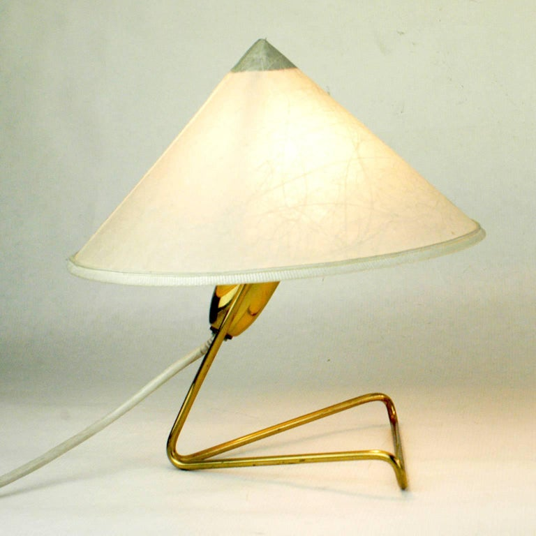 Amazing pair of Austrian midcentury brass table lamps with their original paper shades by Rupert Nikoll Vienna. They have been designed in 1952, their model name is eel. The lamps can also be used as wall lights, the two original brass hooks for