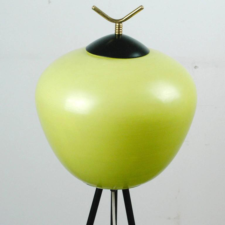 Lovely elegant Italian 1950s tripod floor lamp with yellow  green glass shade, three black laquered iron legs and brass details.