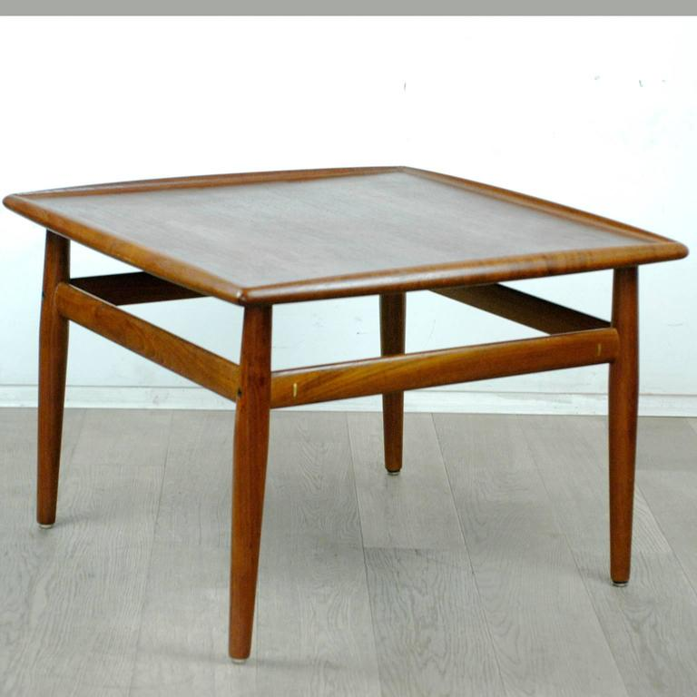 Excellent handcrafted Scandinavian Modern teak coffee table designed by Grete Jalk, with brass details, tabletop with beautiful grain.