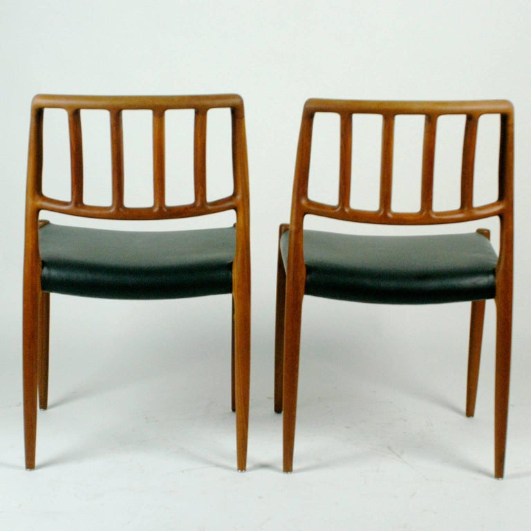 Two sculptural Danish teak dining chairs with black leather seats designed by Niels Otto Möller in the early 70s.  Born in 1920 in Aarhus Denmark Moller is famous for his excellent designs and craftmenship of furniture He founded his own manufactury