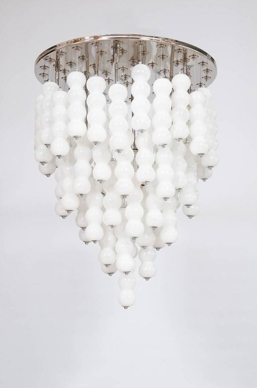 Elegante, and Massive, Italian Venetian, Chandelier, blown Murano Glass, White boll Chains, composed by elegant long white glass elements suspended with a thread of steel, with an adjustable height, all is supported by a chromed frame. Each element,