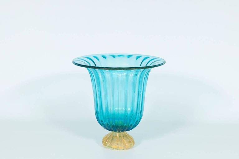 Italian Vase in Murano Glass Light Blue and Gold 1980s. This a very cue vase, in light blue color and gold finishes, composed from a gold striped base and by a light blue striped bowl with gold submerged.  The vase is entirely handcrafted in blown