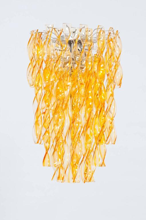 Gorgeous Italian Venetian Murano glass chandelier in very excellent original condition 1990s, composed by light-orange twisted glass elements, all is supported by a grey frame. The chandelier is 33.46 inches high, by 19.69 inches diameter and having