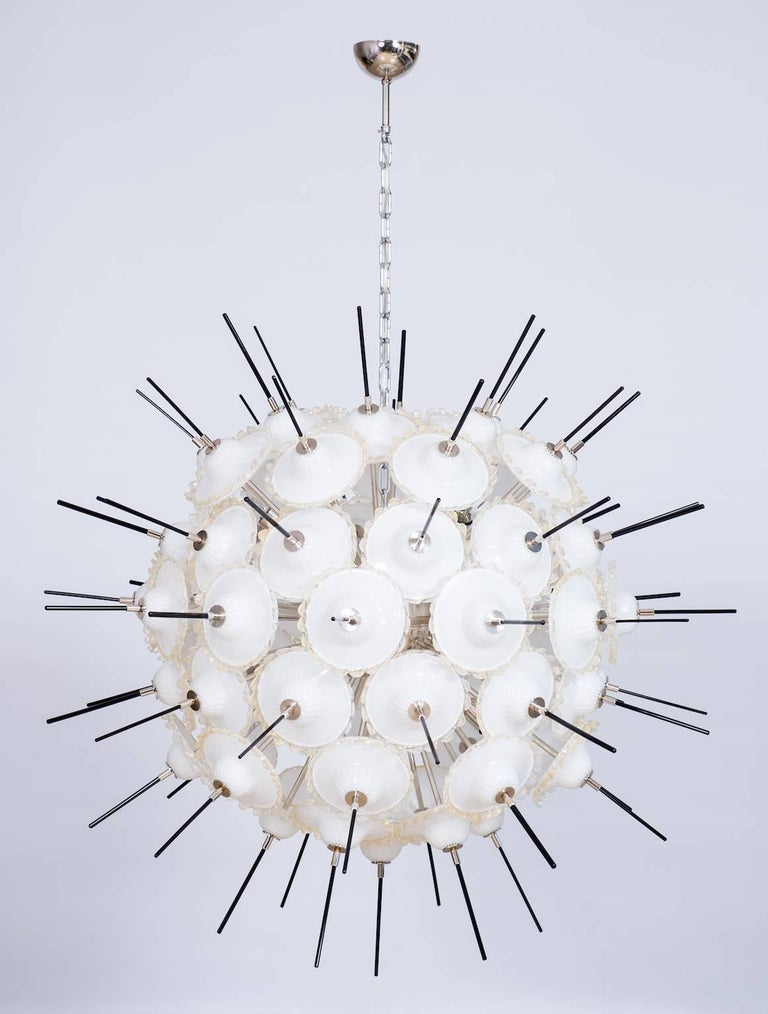 Italian Sputnik chandelier in Murano glass, composed of white circular glass elements with a 24-karat gold edge, and with in the middle a black glass stem, all is supported by an elegant chrome frame. The chandelier is made in the Murano island of