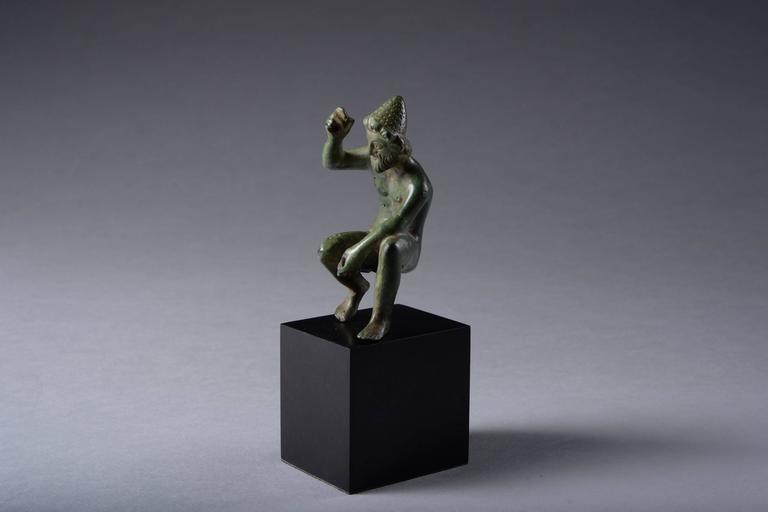 An ancient Greek bronze figure of Hephaistos, god of fire, dating to the 5th-3rd century BC.  Hephaistos is shown seated, nude apart from a pointed craftsman's cap on his head. He rests with his weight on his left foot, his left arm extended to