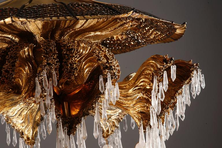 Bronze and cut rock crystal pendants, eight-light arms more one central. The jellyfish an ever recurrent theme since ancient times, inspires today's designers by its bewitching form. The shapely contours and slender filaments become a pretext for