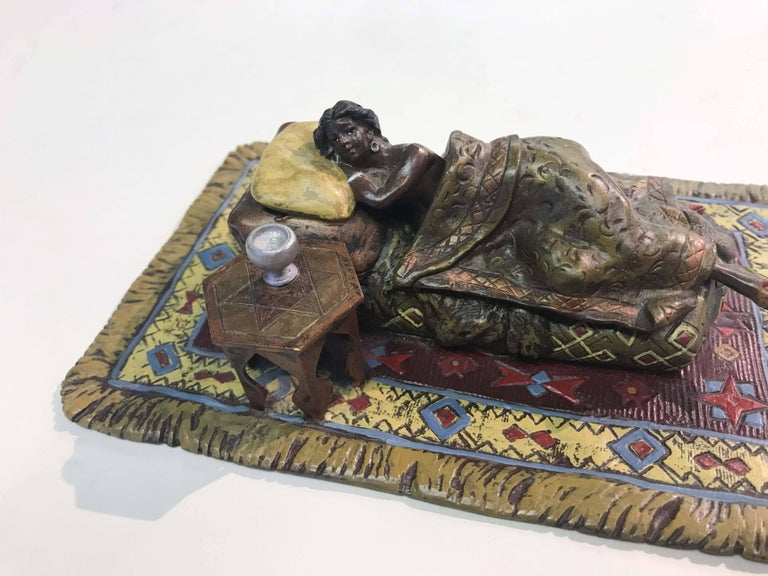 A finely detailed figure of a naked sleeping beauty who shows all when the blanket is lifted. Likely by Franz Bergman although it is marked with a fleur-de-lis, stamped into the base. She has a slight abrasion on her left buttock where the bronze