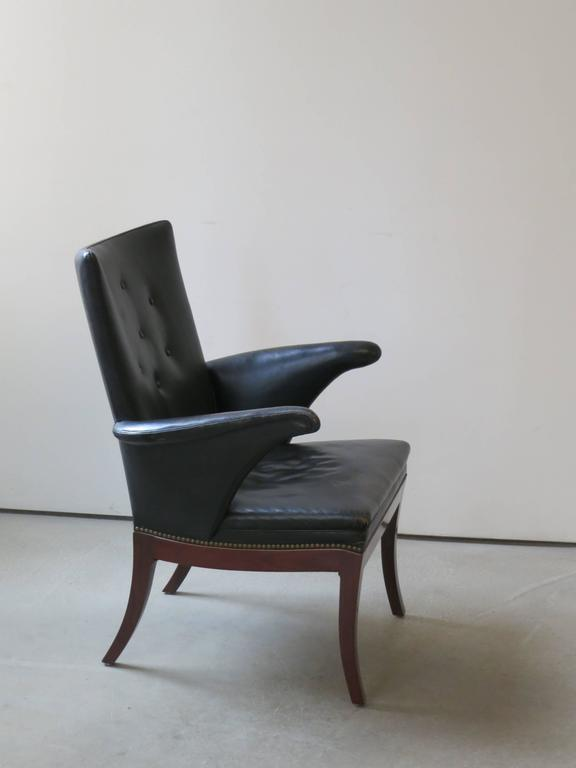 1930s Armchair in Original Black Leather by Frits Henningsen. This chair, which dates to the 1930s, retains its original patinated black leather upholstery and brass nailheads.
