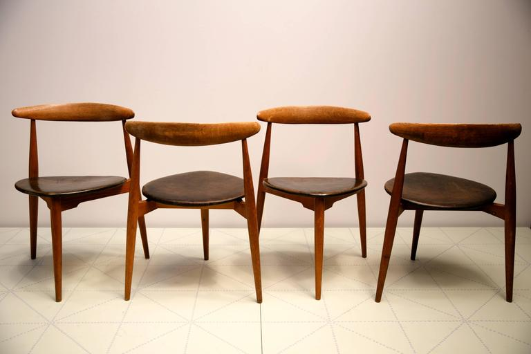 """Offered by Vance Trimble, Set of Four Stacking """"The Heart"""" Dining Chairs, Model FH-4103 by Hans Wegner. These compact and sculptural three-legged chairs, with a carved, floating, curved back rail, feature beautiful patinated oak frames and seats"""