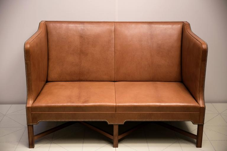 Offered by Vance Trimble, 2 1/2 Person Sofa in Nigerian Goatskin on Cuban Mahogany Legs by Kaare Klint. Made by master cabinetmaker Rud. Rasmussens Snedkerier.  Upholstered in natural Nigerian goatskin with brass nails on Cuban mahogany