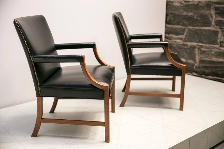 Pair of Armchairs in Black Leather with Brass Nails and Mahogany by Ole Wanscher. These classic and elegant armchairs are upholstered in black leather and fitted with brass nails. Designed in the 1940s and made by master cabinetmaker A.J. Iversen in