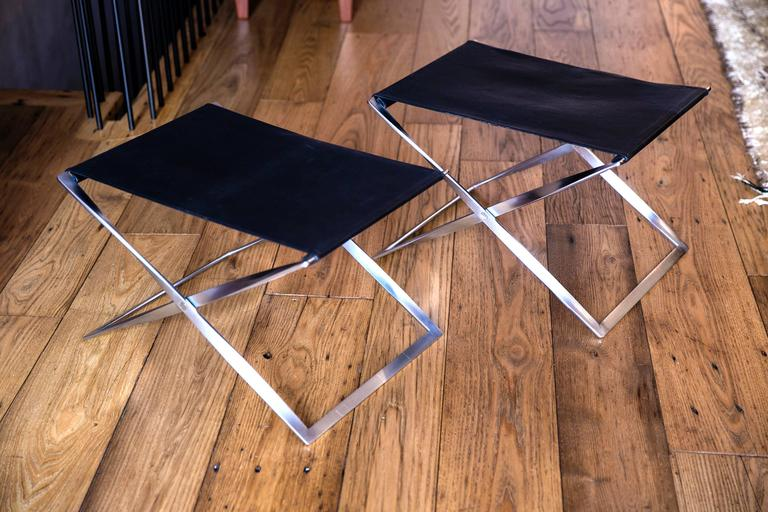 Pair of PK 91 Folding Stools by Poul Kjærholm for E. Kold Christensen. Made by E. Kold Christiansen.  Matte, chrome-plated steel, original black leather seats.  Designed in 1961, Kjærholm took inspiration for his folding stool from many places. He