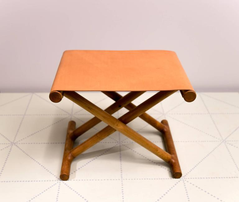 Offered by Vance Trimble, Mogens Lassen's, 1946 Egyptian Folding Stool in Ash and Natural Leather. Presented in 1946 at the Copenhagen cabinetmakers' Guild Exhibition on the stand of cabinetmaker Jørgen Wolff's Møbelsnedkeri, this exquisite
