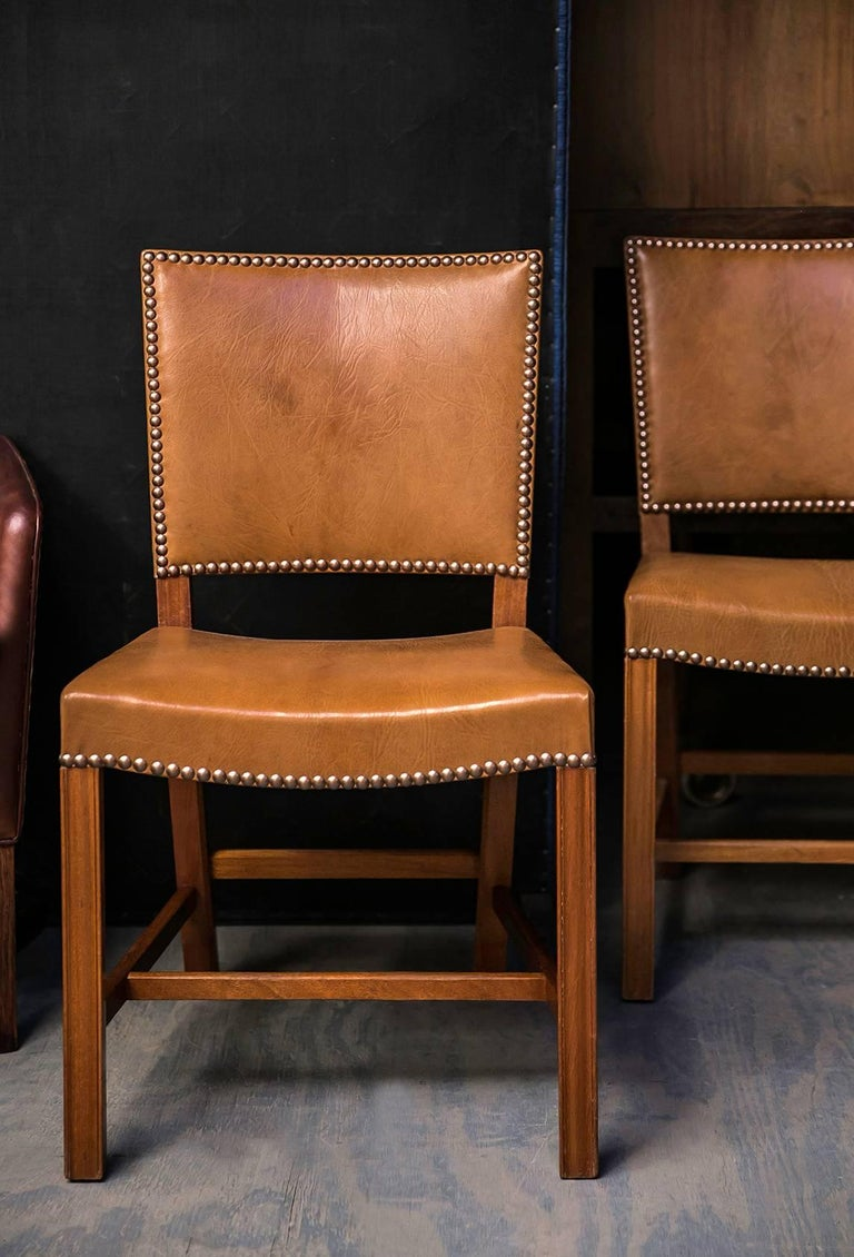 This highly coveted set of chairs by Kaare Klint was made by master cabinetmaker Rud Rasmussen in mahogany and the Nigerian goatskin upholstery with brass nails for which Klint was best known. Nigerian goatskin has an expressive texture that is
