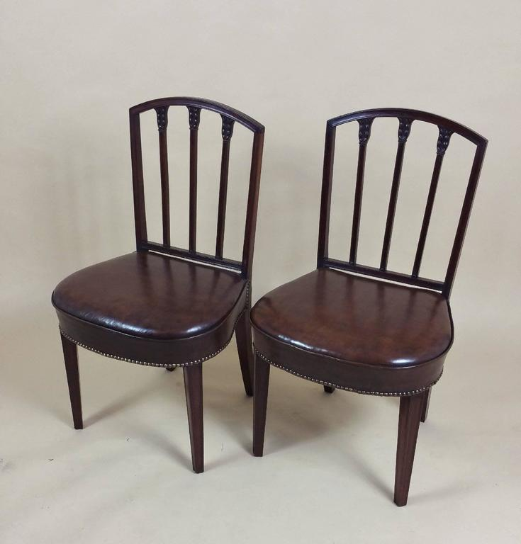 This splendid and rare set of ten English mahogany 18th century. Sheraton dining chairs feature delicately carved honeysuckle on the back splats and very comfortable hide shaped leather seats with brass stud trim. Each chair measures 20 ½ in – 52 cm