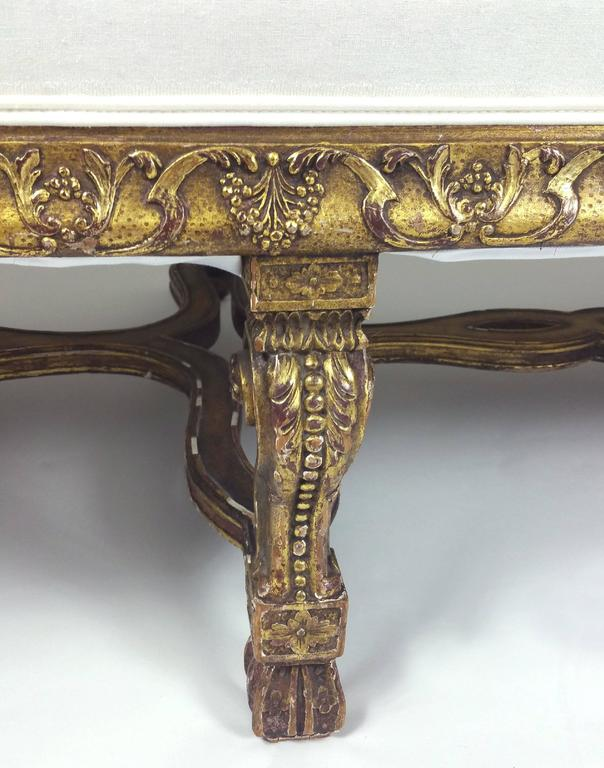 This superb and impressively sizes William and Mary styled carved giltwood settee features exaggerated, scrolled armrest ends and a pierced, shaped under tier. The detailed carving on the base of the seat runs around the entire settee including the