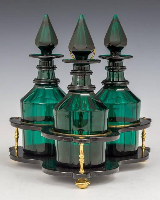 A fine set of three green decanters in black lacquered and brass fitted stand.