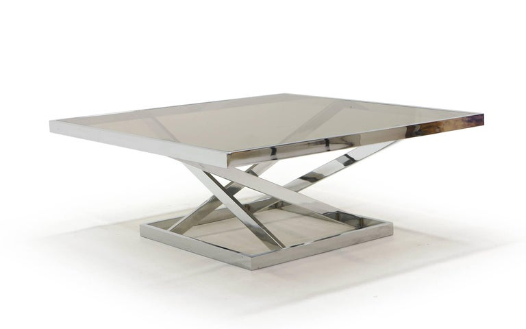Square chrome and glass coffee table with a geometric angular shape to the base like none we have ever seen. The glass insets into the chrome frame. Very striking.