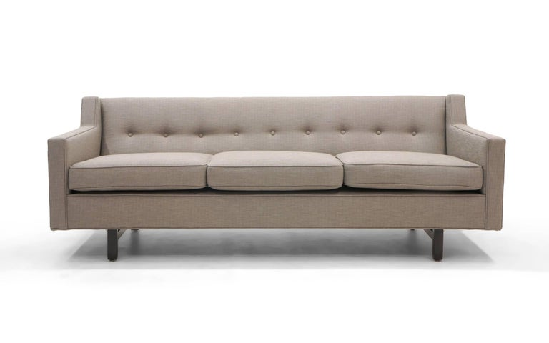 Classic Edward Wormley three-seat sofa. Fully restored and reupholstered in an elegant light gray / grey fabric. Buttoned back behind down filled loose cushions.