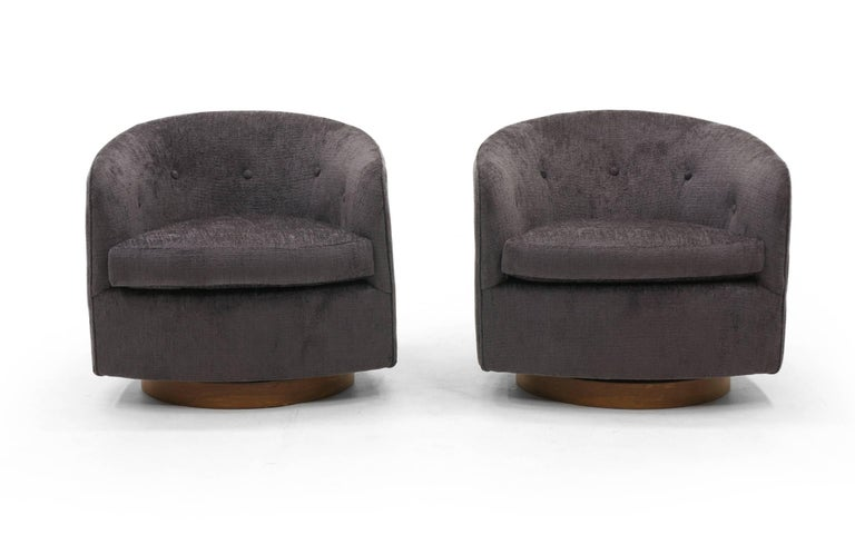 Stunning pair of Milo Baughman for Thayer Coggin's tilt and swivel even arm barrel chairs on walnut bases. These have been completely restored, refinished, and reupholstered in a beautiful, soft, charcoal grey Robert Allen Chenille fabric. The