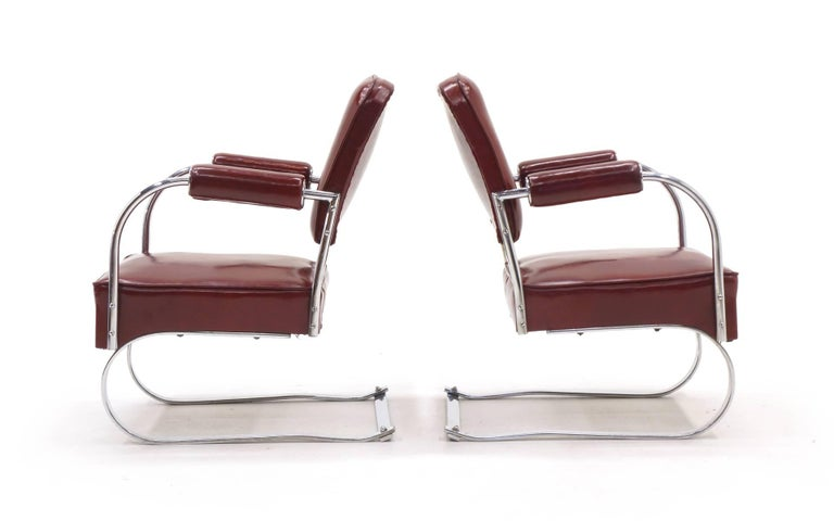 Pair of 1940s tubular chrome and completely original red vinyl lounge/club chairs designed by KEM Weber. These were covered in storage for the past 40 years. There are no tears or obvious wear to the original vinyl.