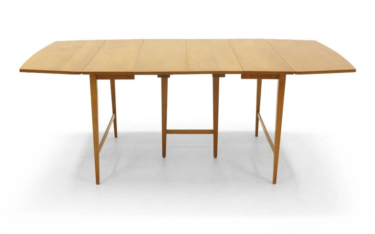 Paul McCobb drop-leaf dining table with center legs for Winchendon Modern with three additional leaves. At its smallest, the table is 24 inch by 40 inch table for two. Each drop-leaf is 15 inches so it extends to 39 inches with one leaf up and 54