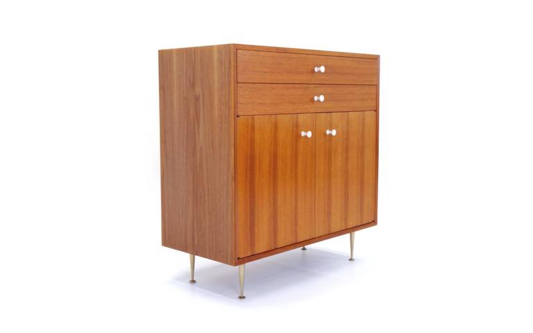 Beautiful walnut George Nelson Cabinet with original porcelain pulls and cast aluminum legs.  From the BCS series, but often mis-referenced as from the Thin Edge Series.  Nearly flawless, excellent condition.