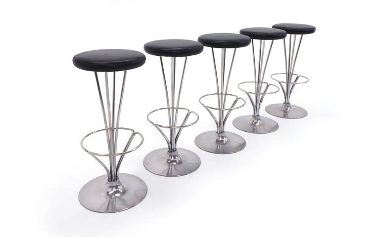 One of the best modern bar stool designs of the 20th century. Super sturdy aluminum and chromed steel construction with expertly reupholstered black leather seats. Signed Fritz Hansen. 31.25 inches tall, base diameter is 13.5 inches and seat