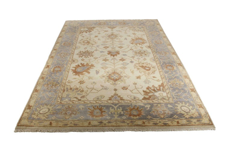This is a beautiful vintage hand knotted rug in the Turkish Oushak taste, not an original Oushak but beautifully conceived after the originals. It boasts a mellow palette with a steely blue low saturation border with twists of geometrical vines