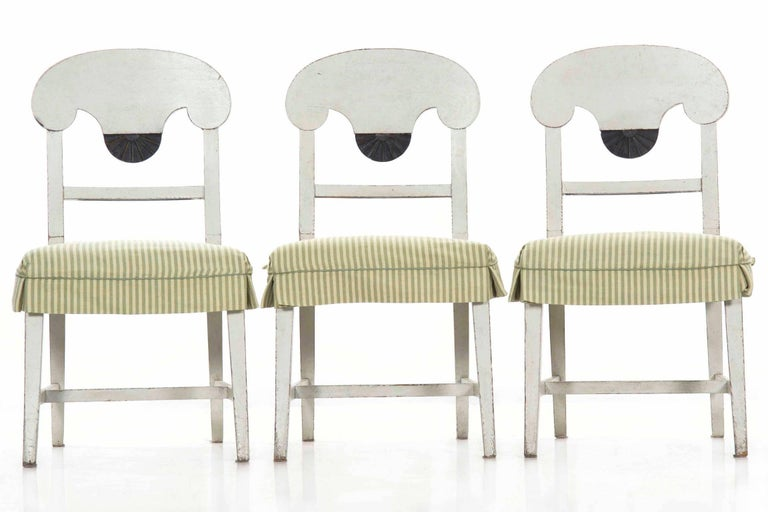This delightful set of six chairs crafted in the Swedish Gustavian taste are finished in a gorgeous and nicely worn mottled white paint. The back of each chair is clearly influenced by the Empire forms of the early 19th century, the dramatic curving