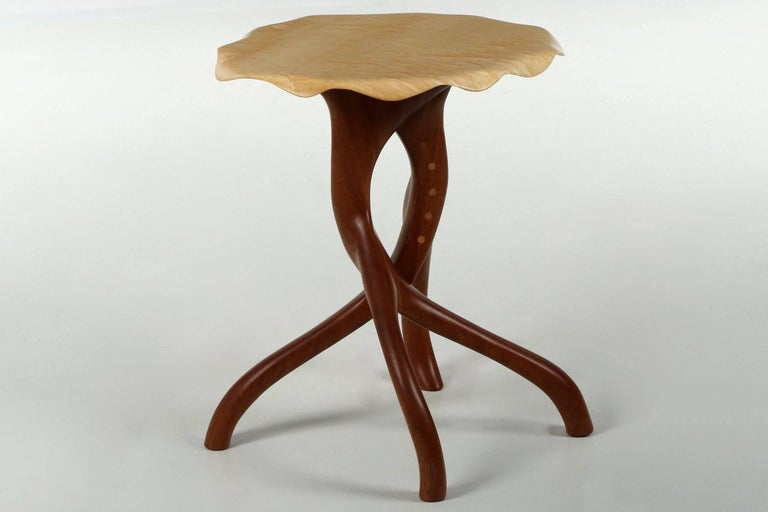 Carved from a single thick block of curly maple, the top of this gorgeous side table ripples like a piece of paper in the breeze. A thin and flawless edging droops over the edges, settling gently in the manner a table cloth would hang from the top.