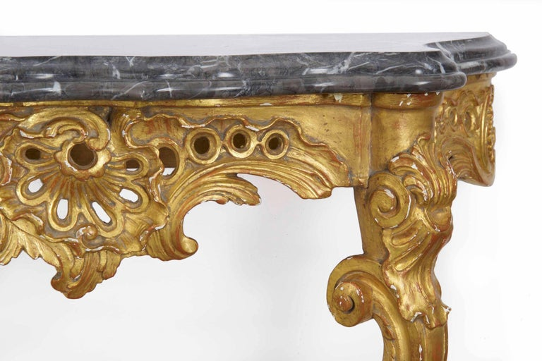 A beautifully carved giltwood console in the Louis XV taste, it was likely crafted during the second half of the 20th century. The marble top is quite attractive and conforms to the curvature of the frame, the lip of the marble layered to give depth