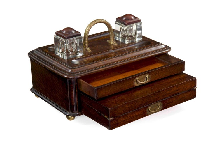 An unusual and most attractive English writing box from the late Victorian period, the box is crafted of beautifully patinated and worn oak. The top has two recesses that cut glass wells rest within, these easily lifting free and portable, each with