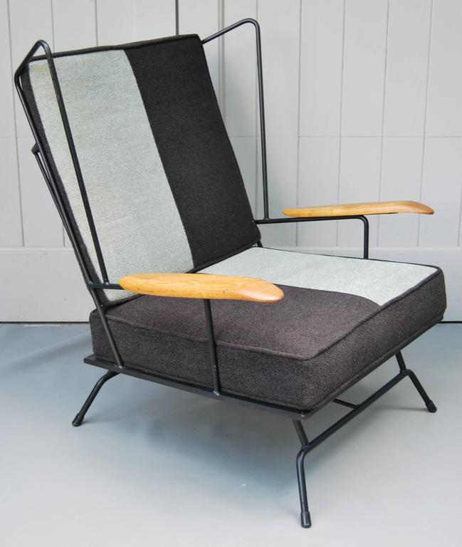 Early 1950s American iron chair with ottoman. Wood armrest. Iron frame has been refinished and cushions are reupholstered in black and grey chenille fabric.