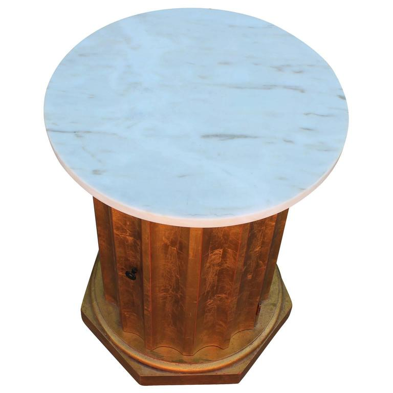 Fabulous Hollywood Regency style fluted column side table. A single door reveals a striking red interior. Table is finished in gold leaf and topped in marble.