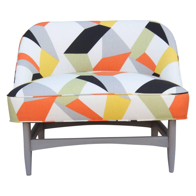 Pair of Kagan or Adrian Pearsall style sculptural lounge / slipper chairs recently upholstered in a bold geometric print that includes orange, black, white, gray and mint green. A single ottoman is also included, making it a perfect lounge set!