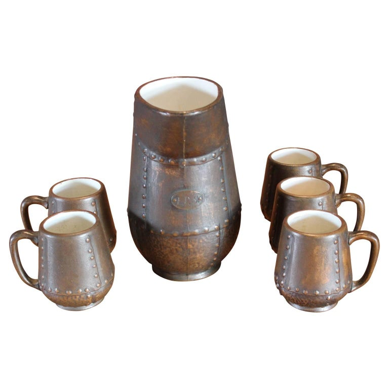Dimensions -  Pitcher:  6.25 in. D x 6 in. W x 10 in. H 9 in. D (from handle to spout)   Cup:  4 in. D x 4 in. W x 4.5 in. H  Clewell was made in limited quantities by Charles Walter Clewell of Canton, Ohio, from 1902 to 1955. Pottery was