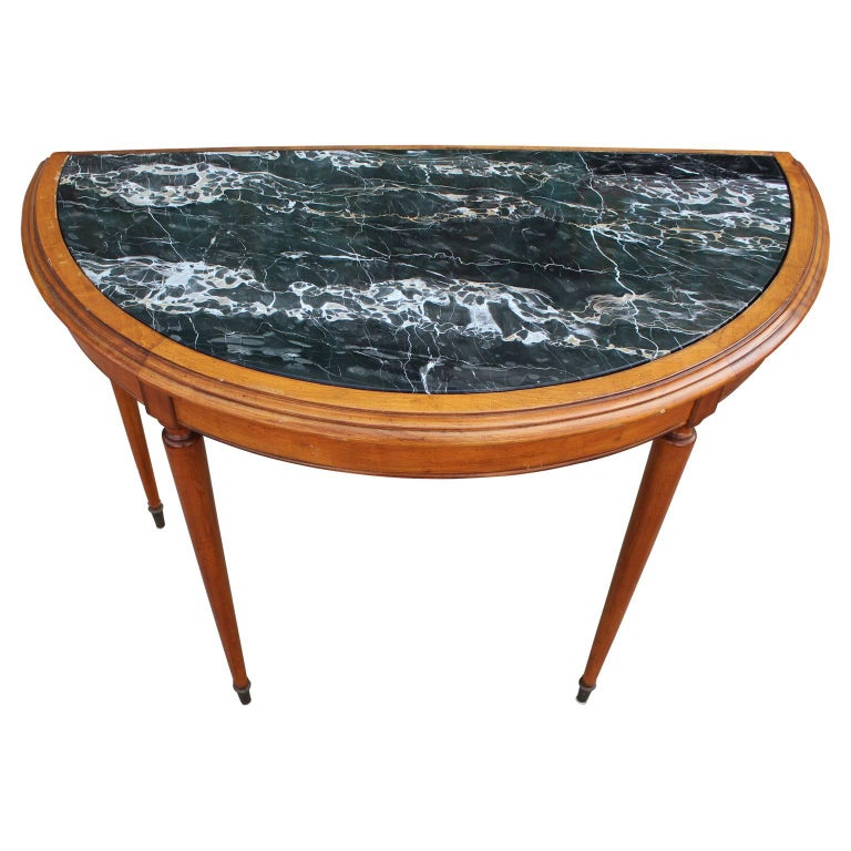 Gorgeous French demilune console or entryway table with a marble top and brass hardware. In the style of Baker Furniture Co.