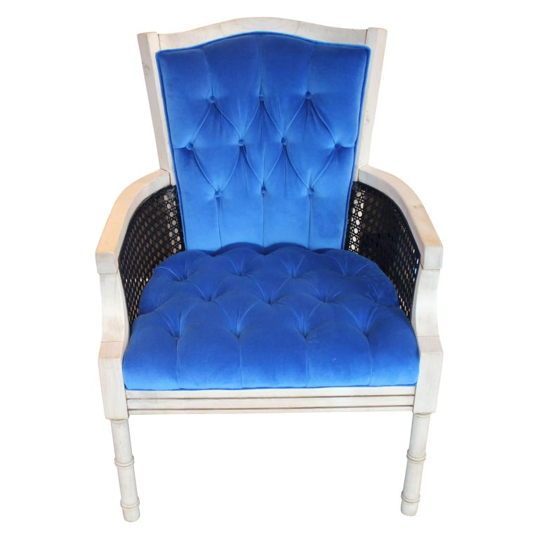 Lovely French cane lounge chair freshly upholstered and tufted in a lush blue velvet. The combination of the dark cane sides with the bleached wood frames offers a lovely contrast. The cane is in wonderful condition.