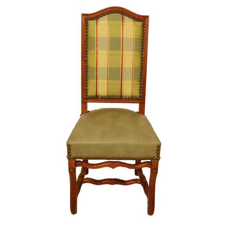 Set of eight, circa 1920 French country elm dining chairs with arched backs, cabriole legs and shaped stretchers. Chairs feature large antique brass nailhead trim. Seat, measures: 19.5