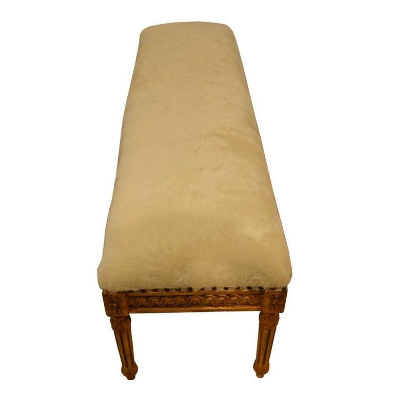 Louis XVI gold gilded bench featuring Classic fluted legs and a floral motif. The bench is upholstered in a cream mohair, with added nailhead studs.  Seat height is 22.5