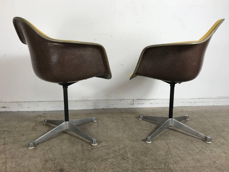 Aluminum Pair of Charles and Ray Eames Swivel Padded Arm Shell Chairs, Two-Tone For Sale